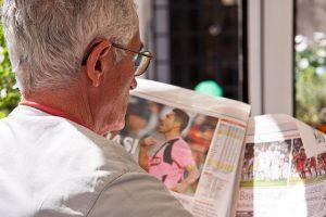Ikääntynyt mies lukee sanomalehdestä urheilu-uutisia.